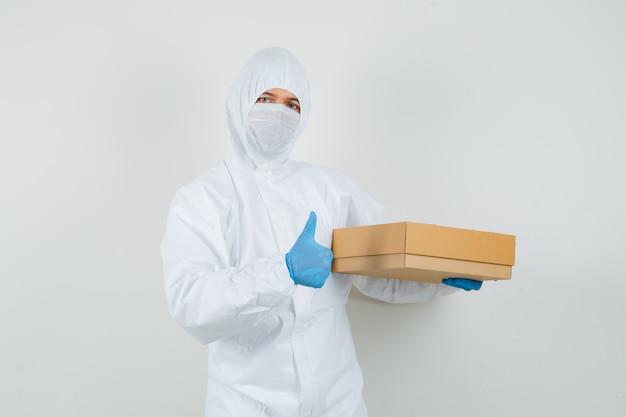 Мужчина-врач в защитном костюме, перчатках, маске, держащей картонную коробку