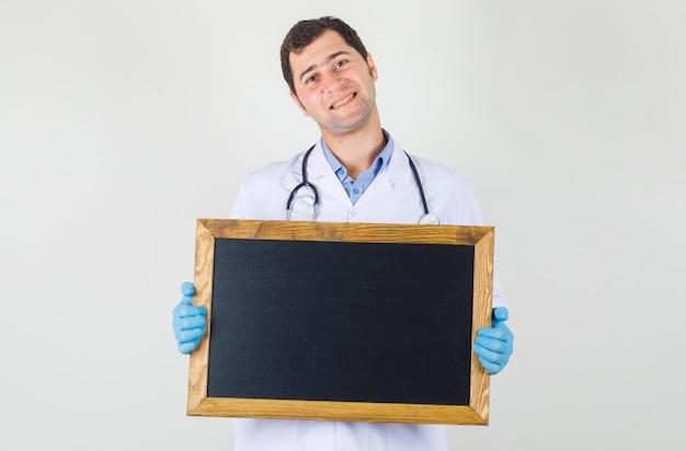 白衣を着た男性医師、黒板を持って陽気に見える手袋