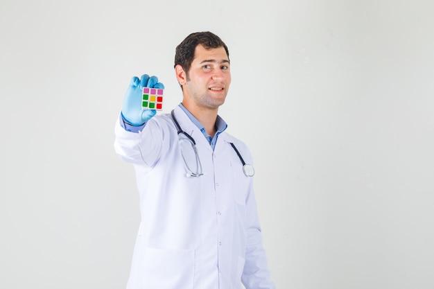 Мужчина-врач в белом халате, перчатках держит кубик рубика и выглядит веселым