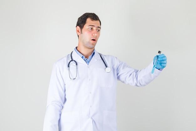 白衣を着た男性医師、試験管を保持し、驚いて見える手袋