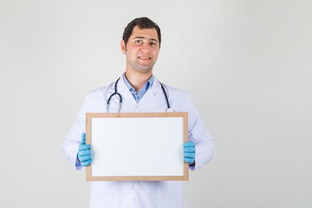 白衣を着た男性医師、ホワイトボードを保持し、陽気に見える手袋