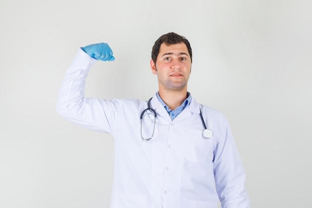 白衣を着た男性医師、腕の筋肉を示し、強く見える手袋