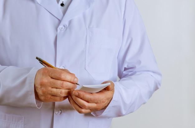 Врач-мужчина в белой медицинской форме делает заметки по рецепту в письменной форме пациента на консультации в клинике