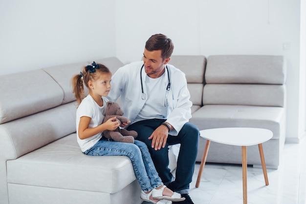 흰색 제복을 입은 남자 의사가 어린 소녀와 함께 병원에 앉아 있습니다.