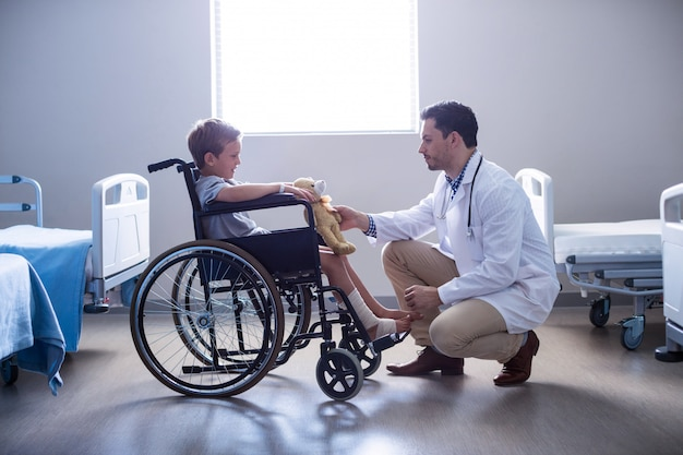 病棟の小児患者と相互作用する男性医師