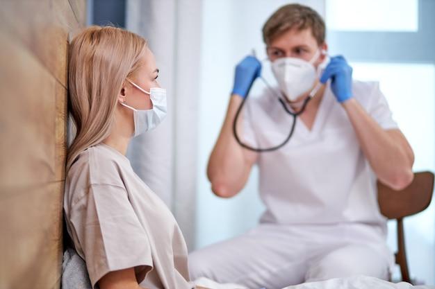 남성 의사는 청진기를 사용하여 침대에 누워 아픈 환자를 검사 할 것입니다. 바이러스의 가정 치료. 코로나 바이러스 감염병 세계적 유행. 코로나 19 발생. 마스크의 여성에 초점