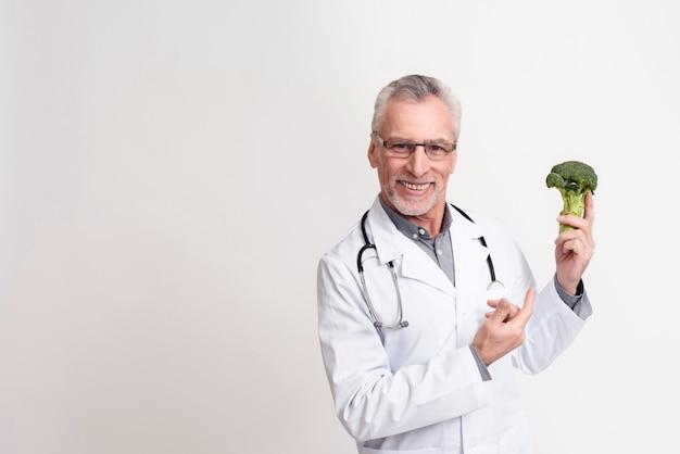 남자 의사는 건강 한 브로콜리를 잡고있다.