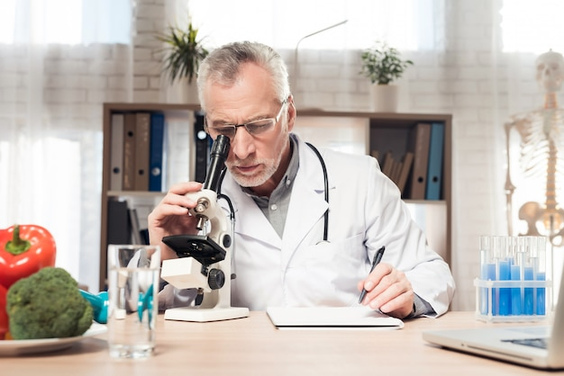 Male doctor is looking in microscope