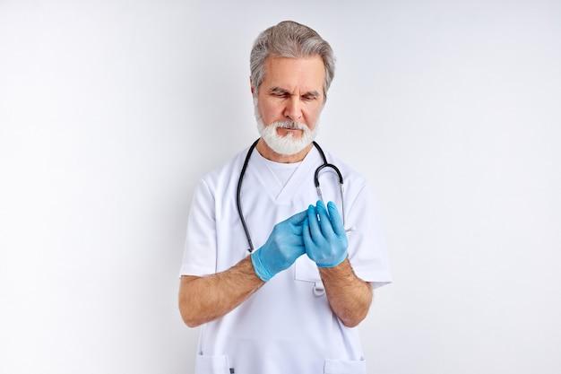 Врач-мужчина в стерильных перчатках, подготовка к работе, с помощью стетоскопа
