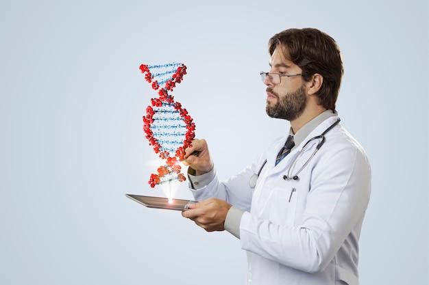 灰色の壁にタブレットから出てくる仮想dnaを見ている男性医師