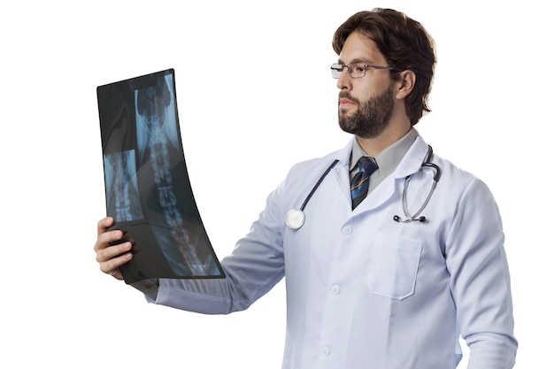 Врач-мужчина смотрит на рентгеновский снимок на белой стене