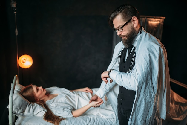 Male doctor measures the pulse of young sick woman