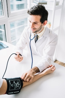 Male doctor measuring patient's blood pressure with stethoscope
