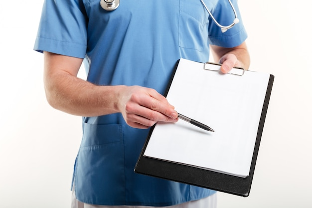 Male doctor or medical nurse pointing with pen to blank page clipboard