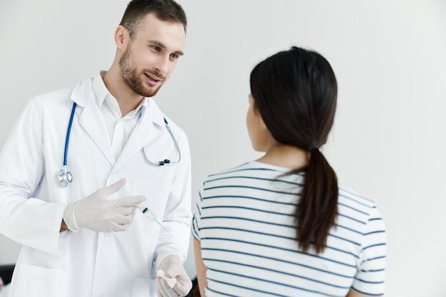 예방 접종을 들고 환자 옆에있는 남자 의사