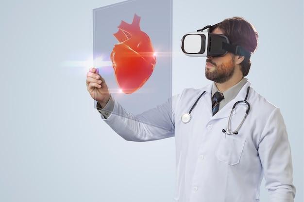 Мужчина-врач на сером фоне с помощью очков виртуальной реальности, глядя на виртуальное сердце.