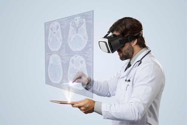 タブレットから出てくる仮想画面を見ている灰色の壁の男性医師