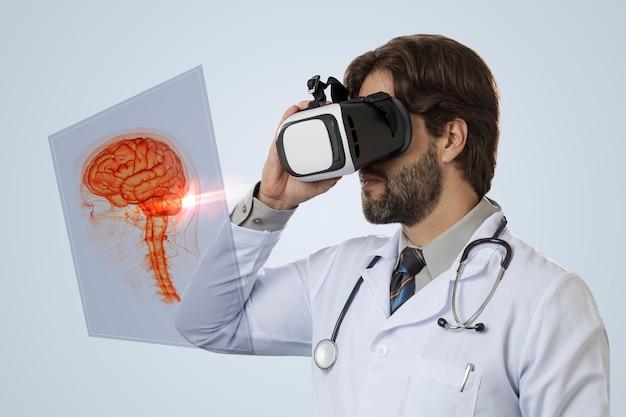 灰色の壁に仮想現実メガネを使用して、仮想脳を見ている男性医師