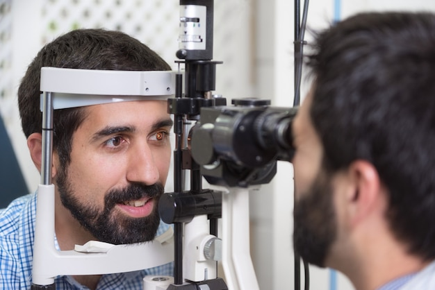 Male doctor ophthalmologist is checking the eye vision of handsome young man in modern clinic