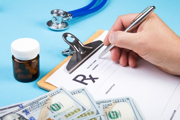 Male doctor or pharmacist holding jar or bottle of pills in hand on a background of dollars banknotes and writing prescription on a special form. medical costs and healthcare payment