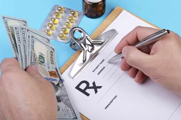 Male doctor or pharmacist holding money in hand and writing prescription on a special form.