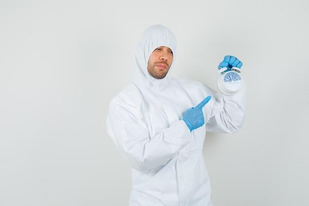 Medico maschio che indica alla sveglia in tuta protettiva