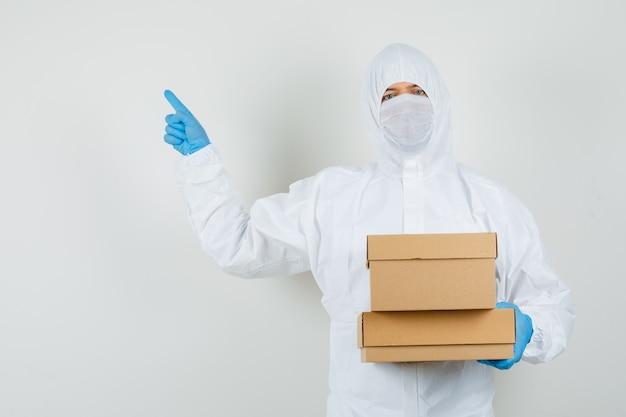 보호 복에 골판지 상자를 들고 멀리 가리키는 남성 의사