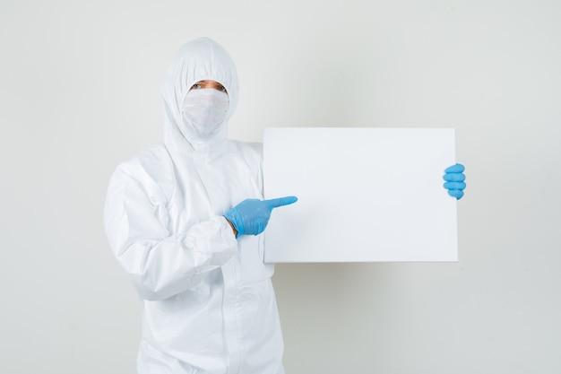 Medico maschio che indica alla tela bianca in tuta protettiva