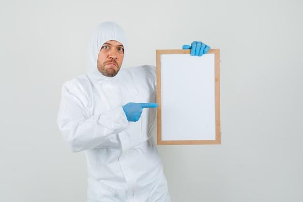 Medico maschio che indica al telaio vuoto in tuta protettiva