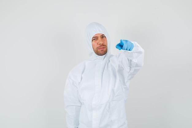 Medico maschio che indica alla macchina fotografica in tuta protettiva