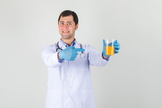 白衣、手袋、陽気に見えるジュースのガラスに指を指している男性医師