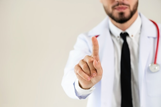 Male doctor pointing finger at blank space.
