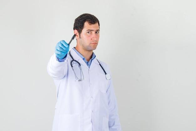 白衣、手袋の正面図でペンを正面に向ける男性医師。