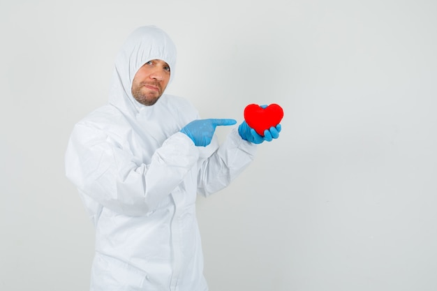 Medico maschio che indica al cuore rosso in tuta protettiva