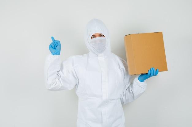 Мужчина-врач, указывая вверх, держа картонную коробку в защитном костюме