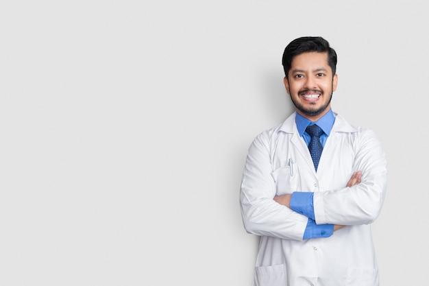 聴診器と白い壁に分離された腕の十字架で笑っている男性医師の肖像画。健康保険の概念。