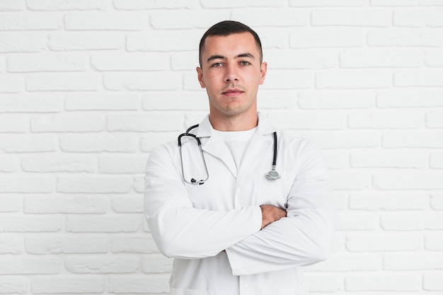 Male doctor posing in front of white bricks wall