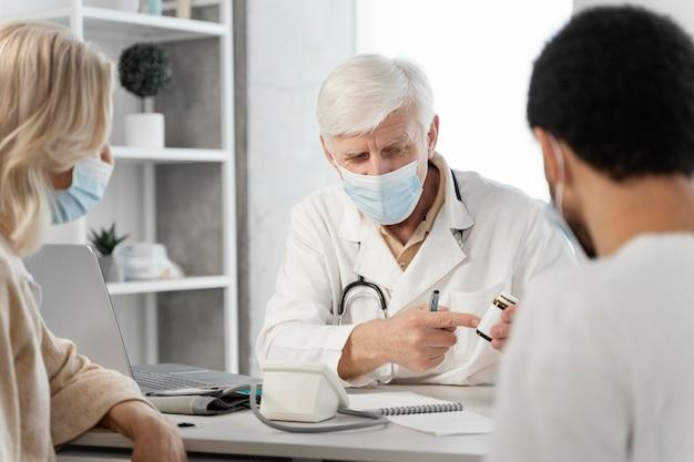 Врач-мужчина прописывает пациенту лекарство