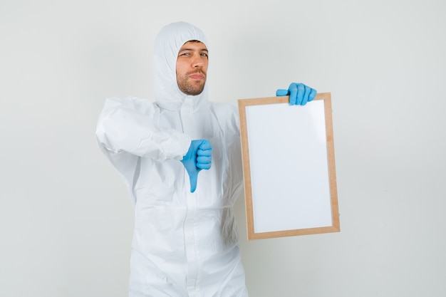 Male doctor in protective suit, gloves holding blank frame with thumb down