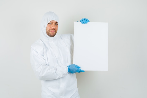 Male doctor in protective suit, gloves holding empty canvas and looking cheerful