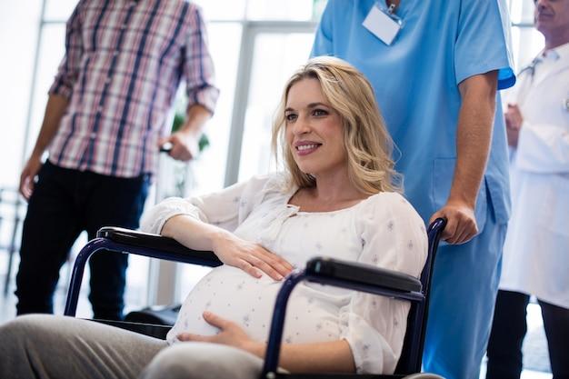 車椅子の妊婦を押す男性医師