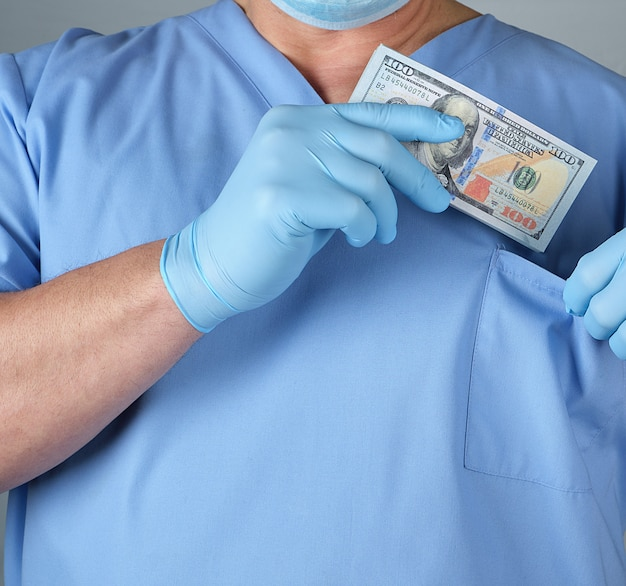 Male doctor puts a wad of dollars in his shirt pocket