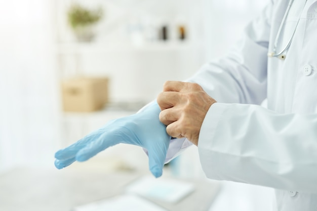 Male doctor putting on blue sterile gloves in clinic