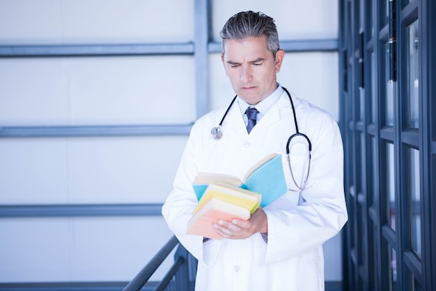 Male doctor reading medical book in hospital
