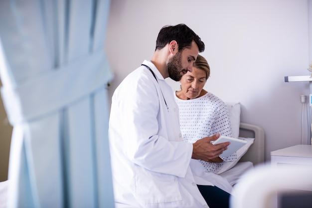 Мужской доктор показывая цифровую таблетку женскому старшему пациенту в палате