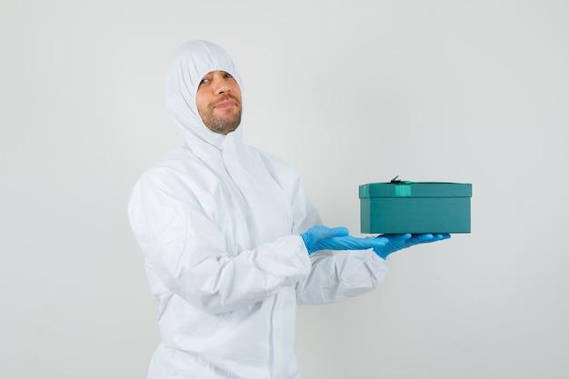 Врач-мужчина показывает коробку в защитном костюме