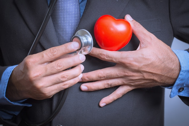 Male doctor showing stethoscope for checkup heart