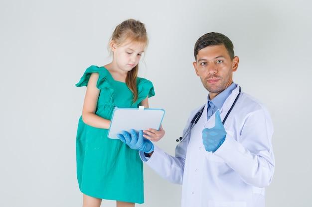子供が白衣を着てボードに書いている間に親指を表示する男性医師