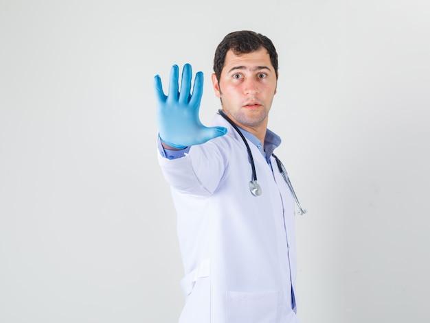 Medico maschio che mostra la mano con i guanti in camice bianco e guardando attento
