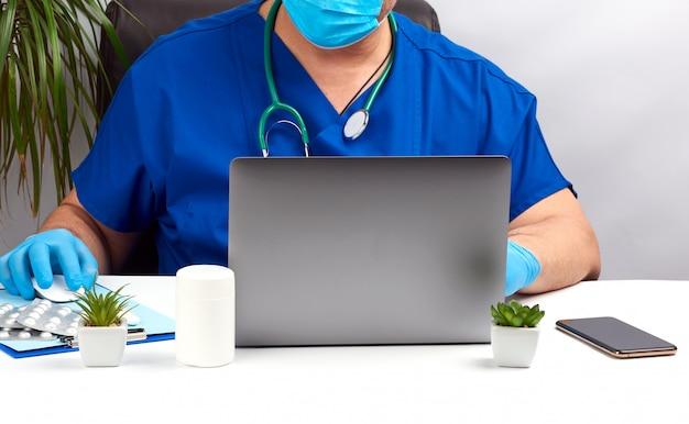 青い制服とラテックスの手袋で白いテーブルに座っている男性の医師